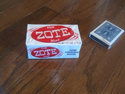 Zote soap shown next to a deck of playing cards to get an idea of its size