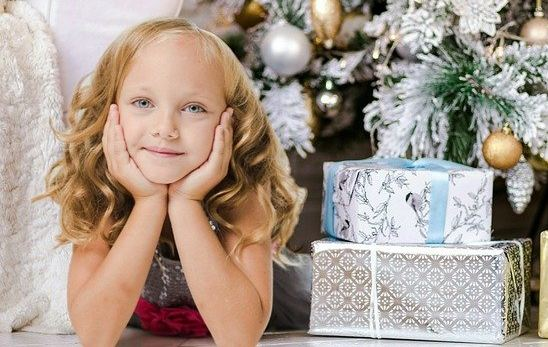 girl near Christmas tree - round-up of shipping dates for delivery by Christmas Eve